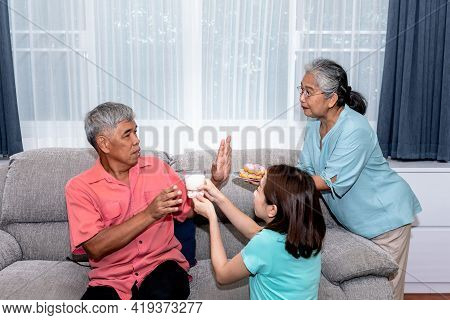 Asian Elderly Man Accepting A Cup Of Milk That His Daughter Gave To, Refusing Dessert His Wife Gave,
