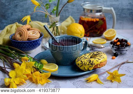 Spring Breakfast. Appetizing Donuts, Cookies, A Cup Of Herbal Tea, Lemons And Yellow Wild Tulips On