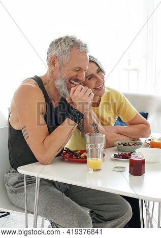 Happy Mature Senior Adult Husband And Older Wife Bonding, Having Fun, Enjoying Eating Morning Breakf