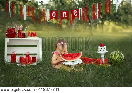 Celebrating A Child's First Birthday In Nature With A Cake And Watermelons. The Girl Bites A Large P