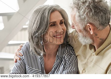 Happy Mature Adult Wife Looking At Affectionate Older Husband Enjoying Talking. Mid Age 50s Romantic