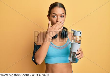 Beautiful hispanic woman wearing sportswear drinking bottle of water covering mouth with hand, shocked and afraid for mistake. surprised expression