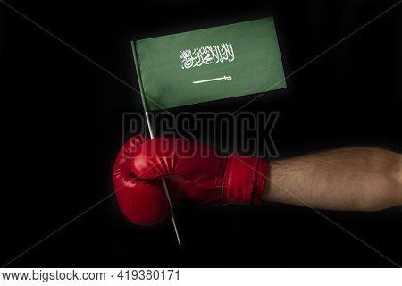Boxer Hand Holds Flag Of Saudi Arabia. Boxing Glove With The Saudi Arabia Flag. Black Background