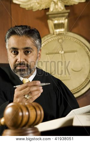 Portrait of judge sitting with book and pen in courtroom