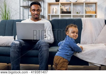 Afro American Man In Casual Wear Working On Laptop And Taking Care Of Little Baby Boy. Young Multita