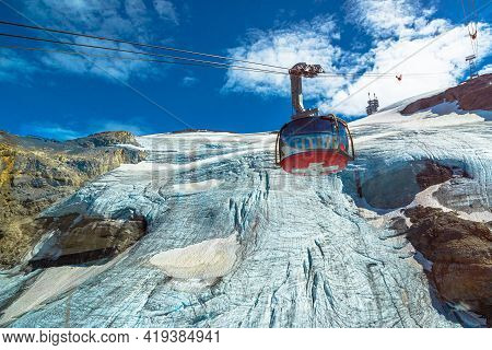Titlis, Engelberg, Switzerland - Aug 27, 2020: Cable Car With Swiss Flag Moving To The Top Of Titlis