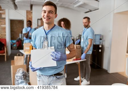 Portrait Of Caucasian Young Male Volunteer In Blue Uniform And Protective Gloves Smiling At Camera,