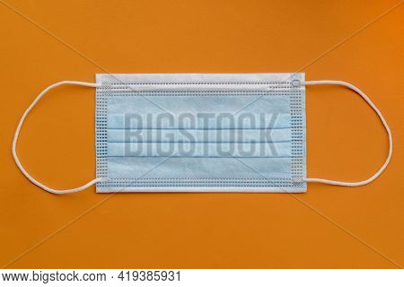 One Medical Surgical Protective Face Mask On Orange Colorful Background