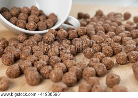 Crispy Chocolate Cereal Flakes Scattered On A Wooden Cutting Kitchen Board