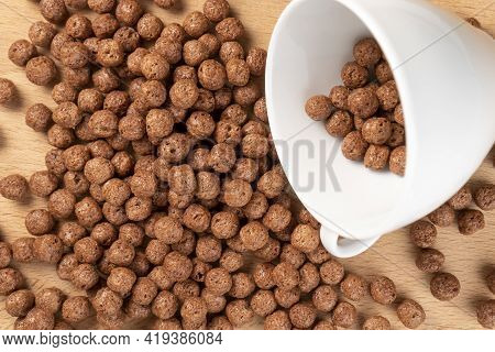 Chocolate Cereal Balls Are Scattered Over The Board With A White Teacup