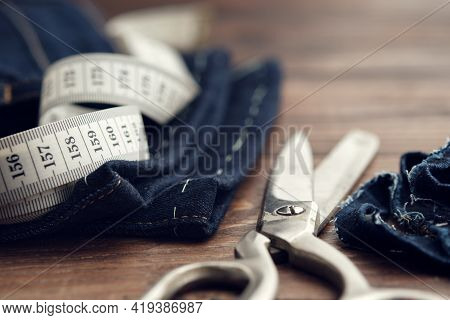 Shortening Jeans. Measuring Tape And Tailoring Scissors On Table. Jeans Cutting.