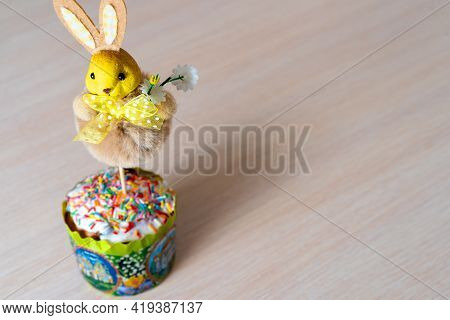 Easter Bunny In A Cupcake On The Table. Background. Postcard. Craft For The Holiday