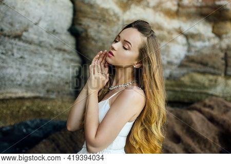 Gorgeous Girl In A Long White Dress On The Ocean At The Beach. The Model Is Inherited By Nature. Gir