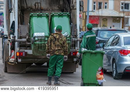 Garbage Truck And Workers Collecting Solid Waste In Residential Area