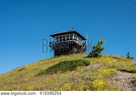 Huckleberry Lookout Tower On Summit Of Peak With Blue Sky