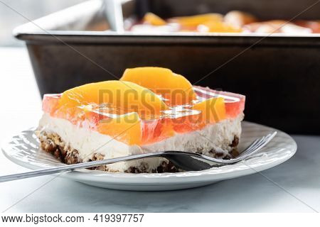 Close Up View Of A Serving Of A Peach Jelly Pretzel Dessert And A Pan With More Of The Dessert In Be