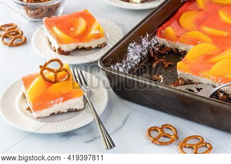 Close Up Of A Slice Of Peach Jelly Pretzel Dessert Garnished With A Pretzel, Ready For Eating.