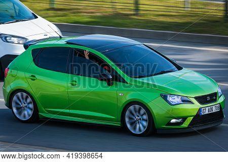 Alanya, Turkey  - April 17  2021:    Green Seat Ibiza     Is Driving Fast On The Street On A Warm Su