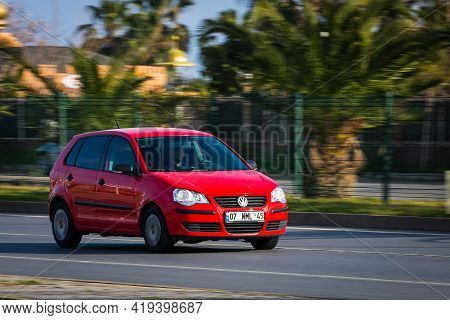 Alanya, Turkey  - April 13  2021:    Red Volkswagen Polo     Is Driving Fast On The Street On A Warm