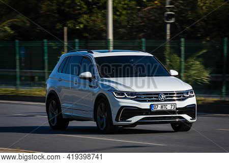Alanya, Turkey  - April 13  2021:  White  Volkswagen Tiguan  Is Driving Fast On The Street On A Warm