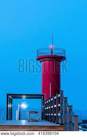Evening View Of Lighthouse With Lit Beacon And Dock Lights On Pier Of Seaport.