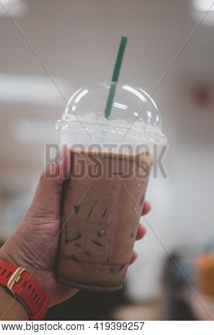 Iced Mocha Coffee In Plastic On Hand In Office Background.