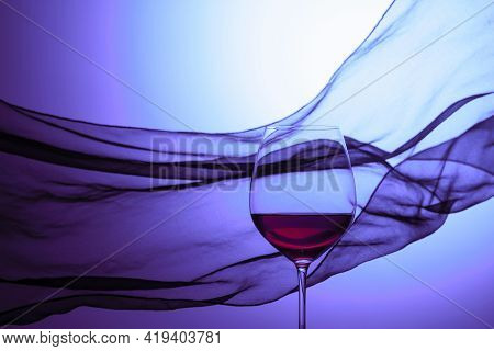 Glass Of Red Wine On A Background Of Waving Satin Curtain. Copy Space.