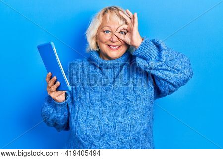 Middle age blonde woman using touchpad device smiling happy doing ok sign with hand on eye looking through fingers
