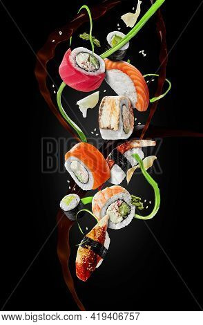 Assorted Sushi With Garnishes Hovering In Air On Black Background