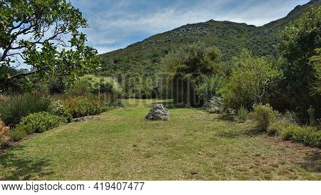 There Is A Picturesque Stone On The Green Lawn In The Park. Around - Tropical Vegetation. Mountain R