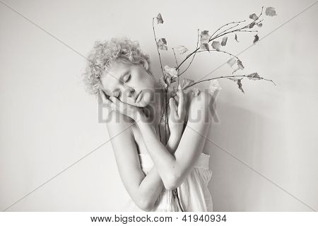 Young scrawny sexy girl with a dry twig in hands, black and white photo.