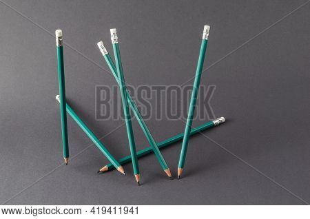 Standing Green Pencils On A Gray Background. A Group Of New Wooden Pencils Are Positioned At Random