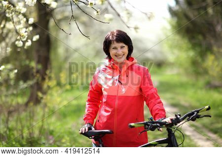 Beautiful Woman On A Bike In A Blooming Spring Garden. Beautiful Mature Woman Posing For The Camera