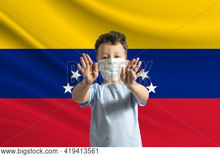 Little White Boy In A Protective Mask On The Background Of The Flag Of Venezuela. Makes A Stop Sign