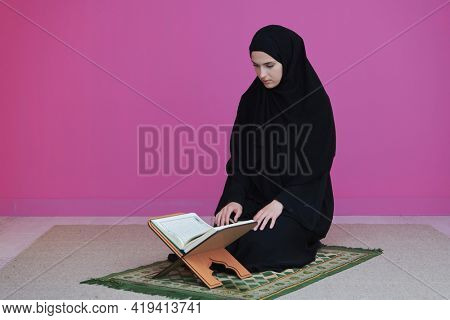 Middle eastern woman praying and reading the holy Quran