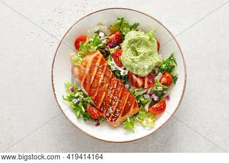Grilled Salmon Fish Fillet And Fresh Green Lettuce Vegetable Tomato Salad With Avocado Guacamole