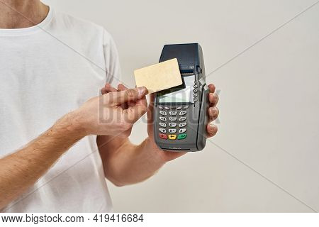 Cut Picture Of A Young Man Applies Credit Card To The Payment Terminal, Young Man Makes A Transactio