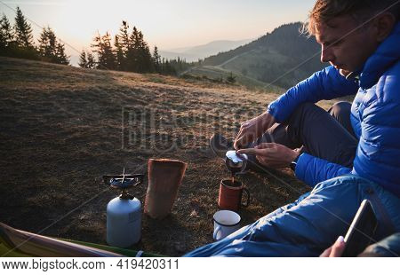 Handsome Young Man Traveler Sitting On Grassy Hill Near Camp Tent And Pouring Hot Drink Into Cup. Ma