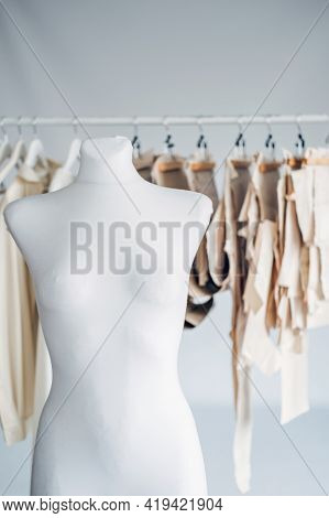 Many Paper Sewing Patterns And Mannequin In Sewing Factory Background. Clothing Pattern, Manufacture