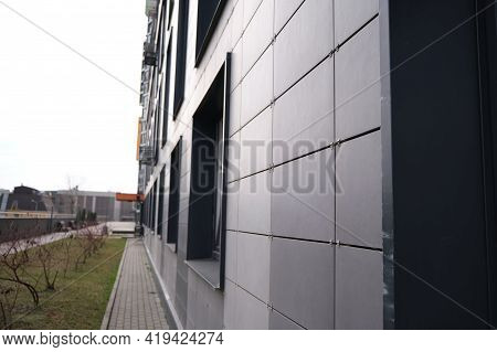 Wall Of Office Building Made Of Metal Plates With Windows. Detail Of Modern Residential Building Win