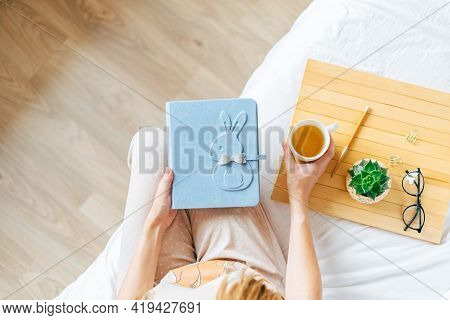 Top View Of Cropped Woman Hands Holding And Watching A Family Photo Album. Mother Sit On Bed And Wat