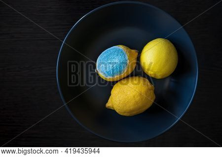 Three Whole Yellow Bright Lemons On A Dark Blue Plate On Wooden Table. One Lemon With Light Blue Tur
