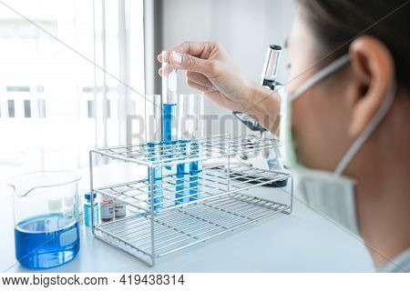 Scientist Woman In Medical Face Mask Is Holding Test Tube With Blue Liquid And Looking Reaction Of E