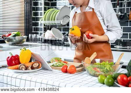 Asian Housewife Holding Bell Pepper And Tomato In Hands During Watching Tutorial Cooking Class Onlin