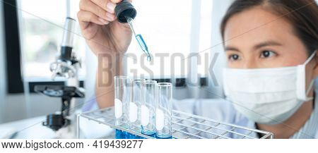 Scientist Woman In Medical Face Mask Is Holding Dropper To Dropping Chemical Liquid Into Test Tube A