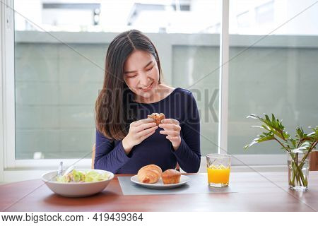 Young Asian Woman Holding And Have A Bit To Eating Bread With A Glass Of Fresh Orange Juice After Ea