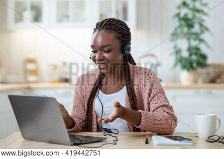 Online Tutoring. Smiling Black Female Tutor In Headset Using Laptop In Kitchen