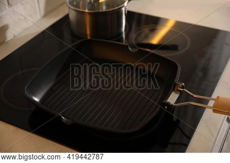 Frying Pan On Modern Cooktop In Kitchen