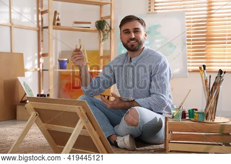 Young Man Painting On Easel With Brush In Artist Studio