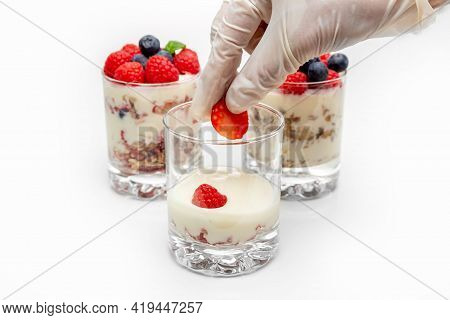 Muesli With Yogurt And Berries In A Glass On A White Background. The Chefs Hand Puts Strawberry Slic